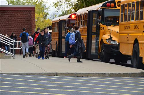 Middle School students leave school to get on the bus.