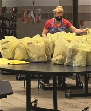 Food service workers sets up bagged lunches.