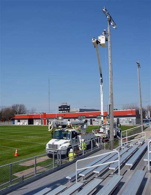 An electrical crew in a cherry picker truck installs guy wires on a pole on the football field.